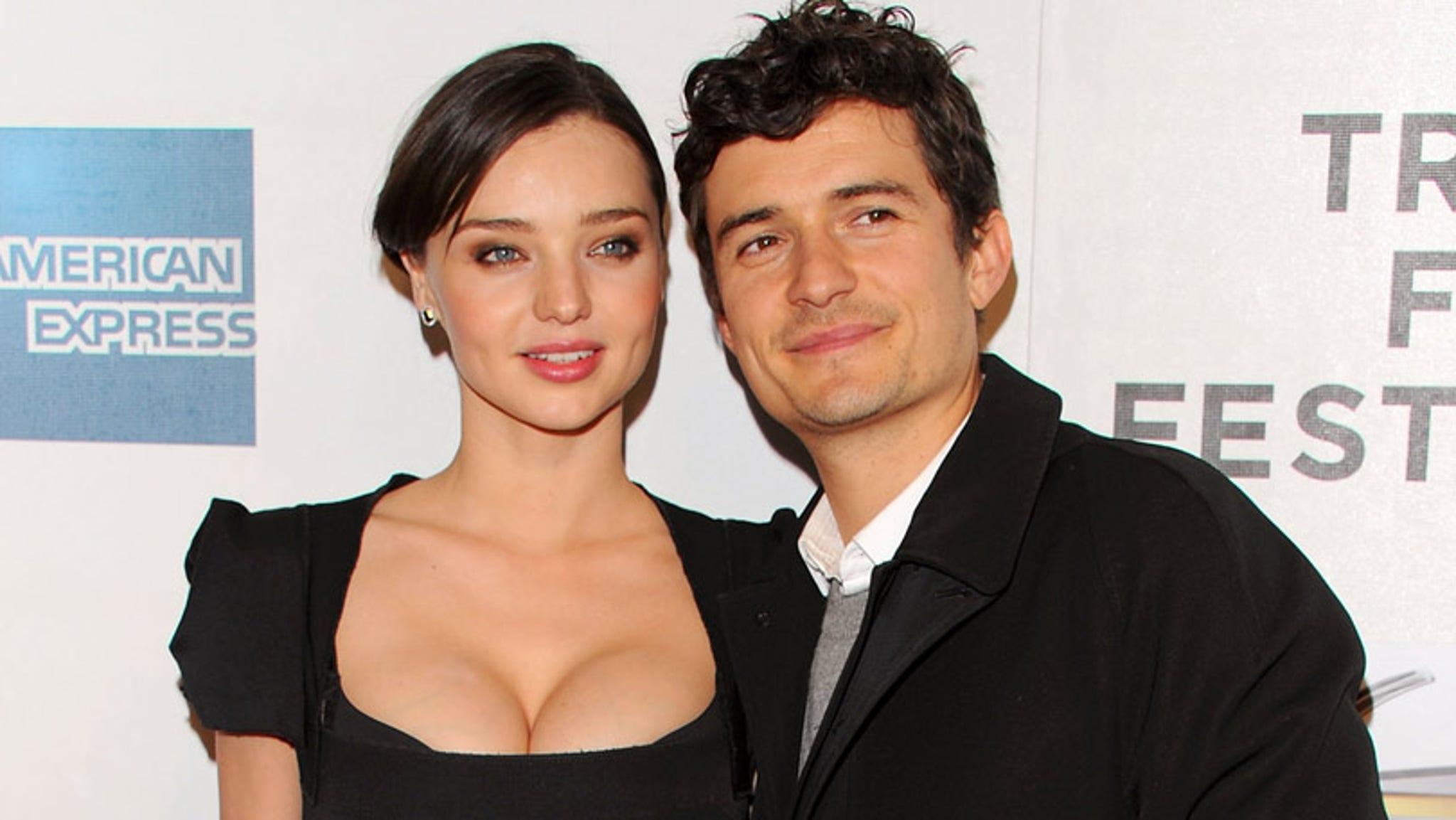 Orlando Bloom points to his naked wedding finger after